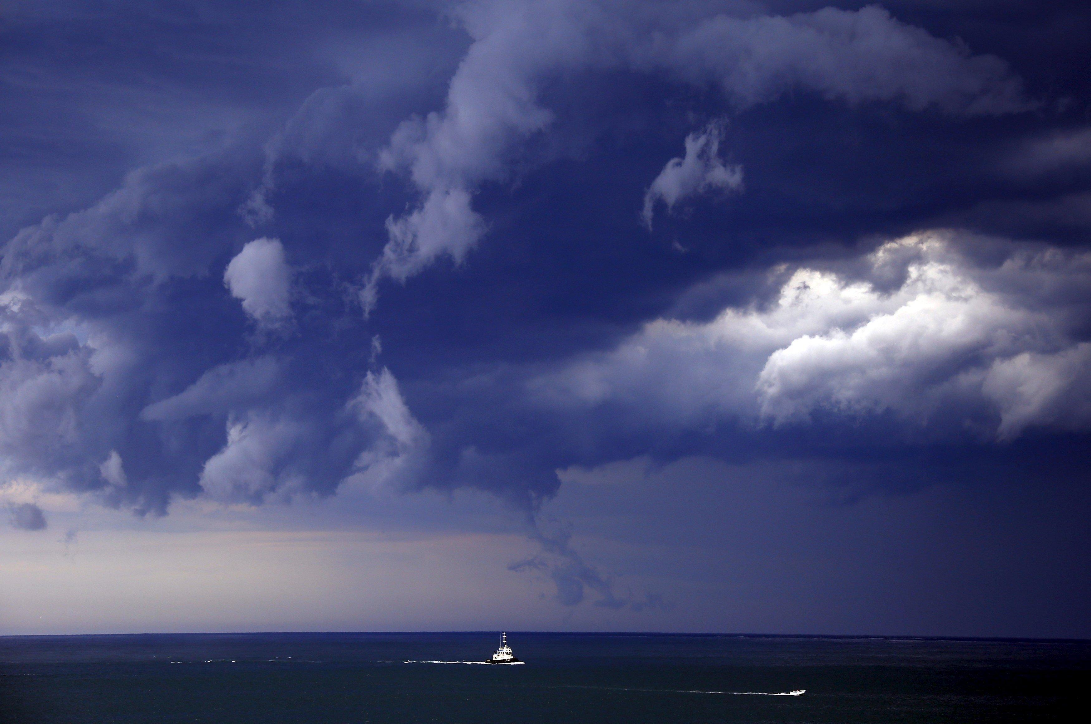 Boats head into shore as storm clouds move along the coast towards the city of Sydney, Australia